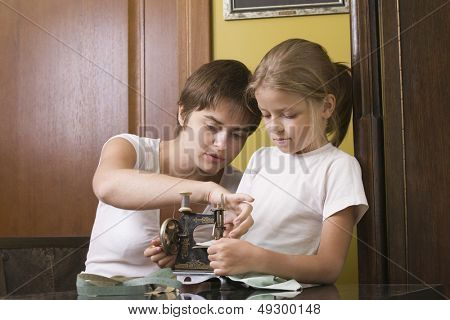 Mother and little daughter using old sewing machine in home