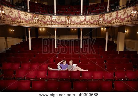 Full length of two young women sitting in theatre stall with scripts