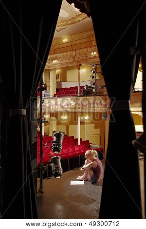 Full length side view of a young woman sitting on stage with script