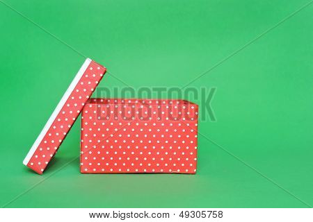 Opens red present box isolated in green background