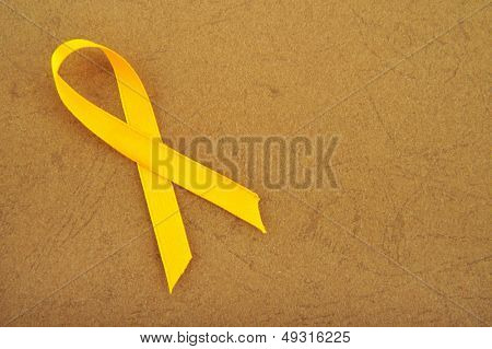 Yellow awareness ribbon on brown background