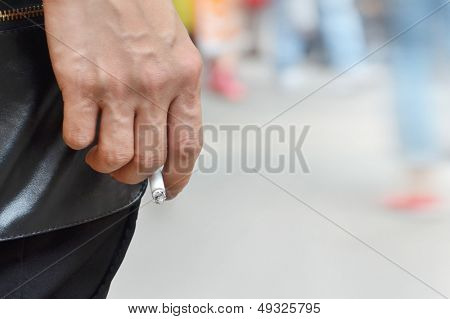 Image of cigarette is in the hand of man