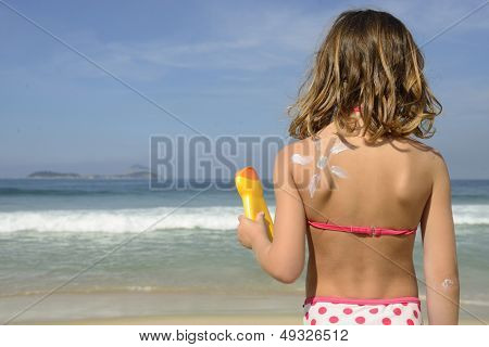 Child with painted sun made of sunscreen on back