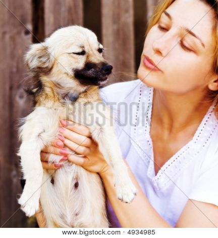 Young Woman Giving A Kiss To Her Funny Dog