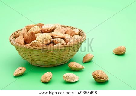 small basket with almonds on green background