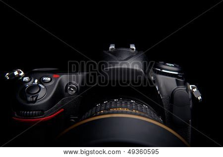 detail of a professional digital photo camera with lens on black background