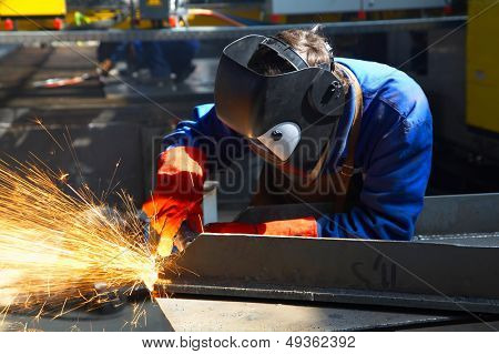 worker with protective mask and gloves grinding/welding metal and sparks spreading