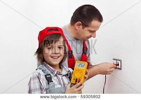 Happy Boy Helping His Father Mounting Electrical Wall Fixtures