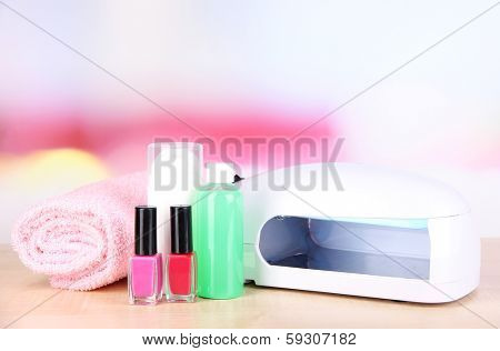 Lamp for nails and accessories for manicure on table on bright background