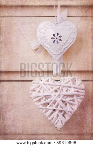 A wicker and a tin heart hanging from the knob of a chest of drawers. Vintage effect with added texture.