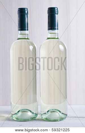 Two Unlabelled Bottles Of White Wine