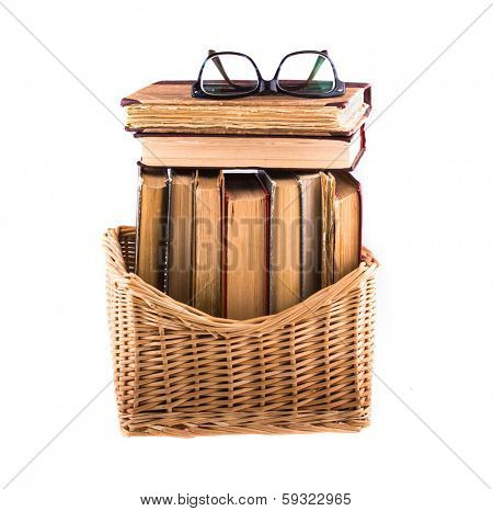 Stack of old antique books in a wicker basket and spectacles lying on top, isolated on white background.