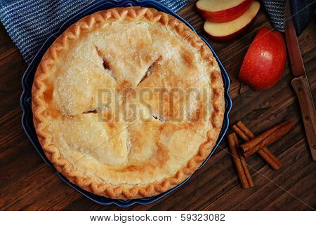 Freshly baked apple pie with cinnamon sticks and vintage knife on rustic, dark wood background.  Low key still life with directional, natural lighting for effect.