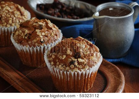 Freshly baked honey raisin muffins in rustic setting.  Vintage pewter dishes with ingredients in background.  Low key still life with directional, natural lighting and shallow dof.