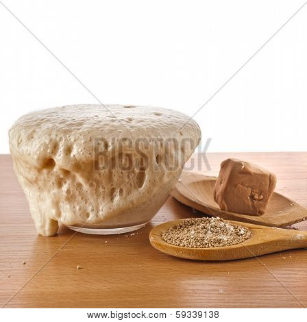 Rising Yeast Dough in bowl isolated on wooden table surface background
