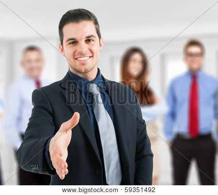 Young succesful businessman giving an handshake. Focus on the hand