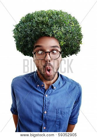 Young cross-eyed man with green bush instead hair