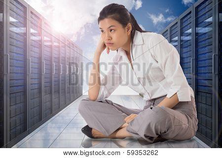 Businesswoman sitting cross legged against server hallway in the sky