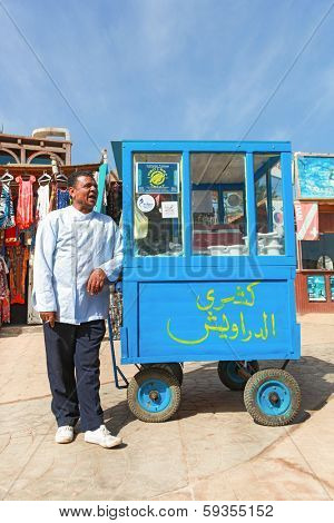 DAHAB, EGYPT - JANUARY 29, 2011: Vendor on the street next to stand. Street food is the cheapest way for tourists to get a meal.