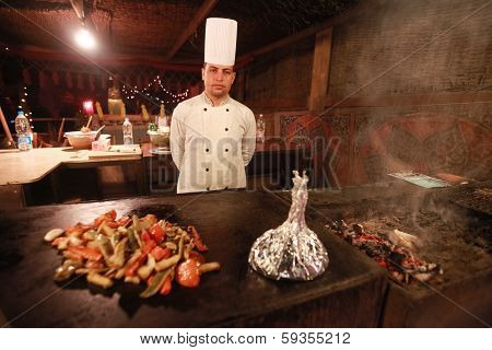 DAHAB, EGYPT - JANUARY 28, 2011: Egyptian cook stands in the kitchen. Egyptian food is a mixture of all the different civilisations that came to Egypt in the history of its existence.