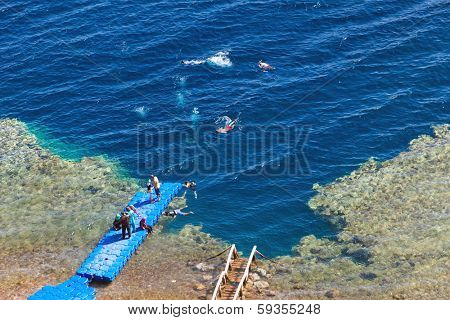 DAHAB, EGYPT - JANUARY 30, 2011: Tourists diving in Blue Hole, popular diving location on east Sinai, a few kilometres north of Dahab on the coast of the Red Sea.