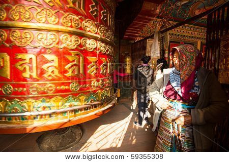 KATHMANDU, NEPAL - DEC 20, 2013: Unidentified pilgrimage near spinning Big Tibetan Buddhist prayer wheel at Boudhanath Stupa. Stupa is one of largest in world, of 1979 is a UNESCO World Heritage Site.