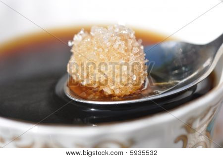 Cup Of Coffee And Dissolving Sugar Lump