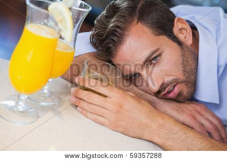 Drunk businessman slumped on bar beside cocktail at the local bar