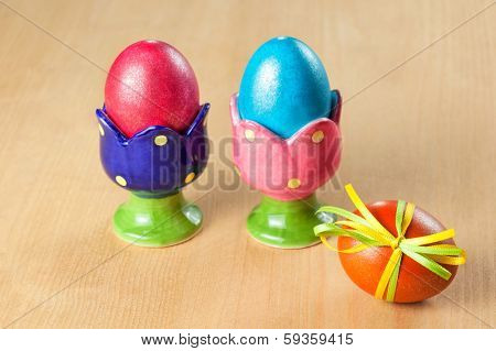 Colored easter eggs in egg cups on wooden table, focus on the foreground