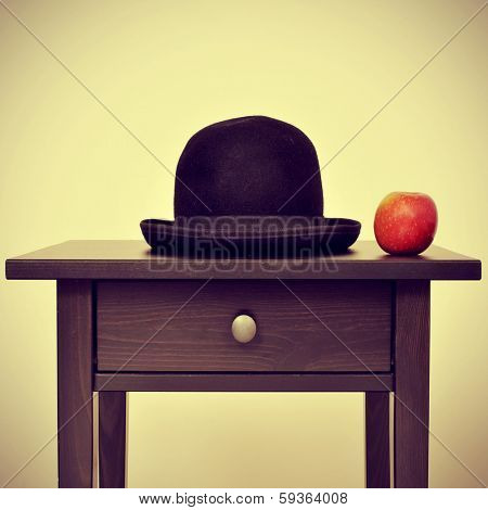 picture of a bowler hat and an apple on a bureau, homage to Rene Magritte painting The Son of Man, with a retro effect