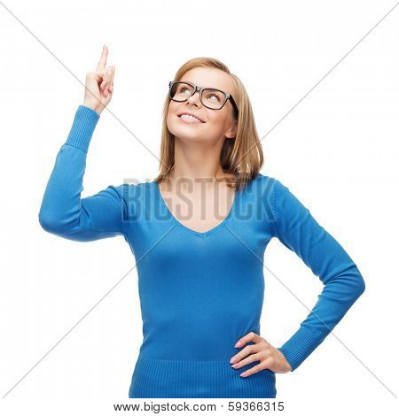 advertisement concept - attractive young woman in casual clothes and black eyeglasses pointing her finger up