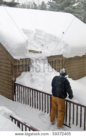 Man removing snow from rooftop
