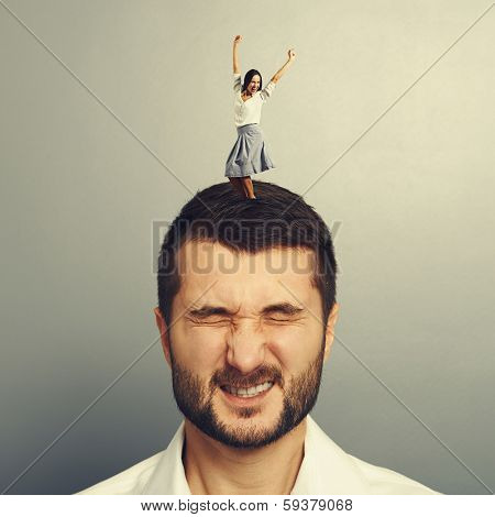 excited young woman dancing on the head of dissatisfied man