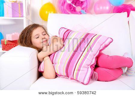 Pretty little girl slipping on sofa on celebratory background
