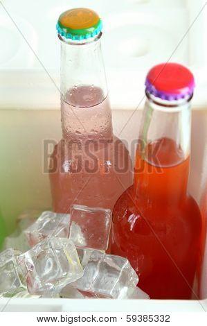 Drinks in glass bottles in mini fridge close up