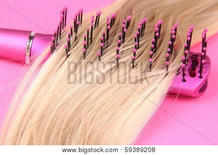 Long blond hair with hairbrush on pink background