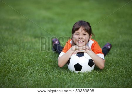 Outdoor photo of cute little girl leaning on soccer ball in green grass