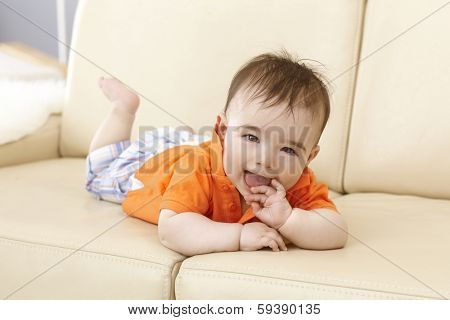 Beautiful baby boy lying on sofa, smiling happy with hand in mouth.
