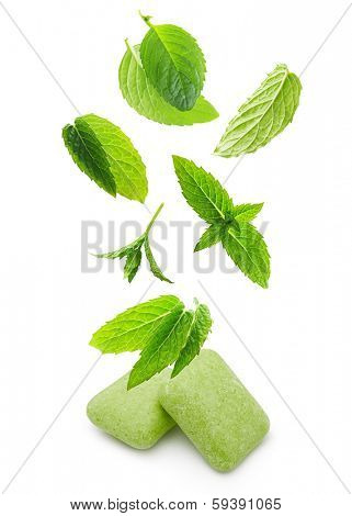 Two chewing gum with mint leaves on white background.