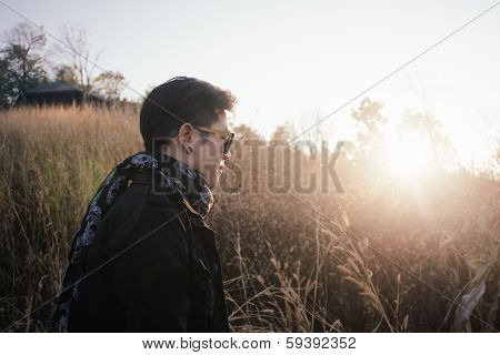 Young Man In Grass Field With Sunrise