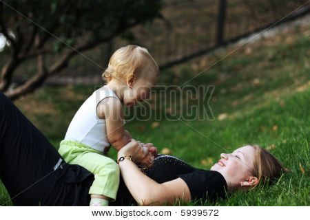 Mother With Sone Play On A Grass