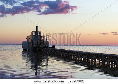 Ferryboat Near The Pier At Sunset