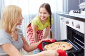 pic of oven  - Portrait of young woman taking pizza out of oven with her daughter standing near by - JPG