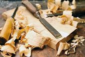 stock photo of workbench  - old wood chisels with shavings on the workbench - JPG