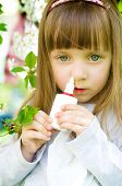 stock photo of nose drops  - Little girl spraying medicine in nose nose drops nose spray - JPG