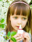 stock photo of rhinitis  - Little girl spraying medicine in nose nose drops nose spray - JPG