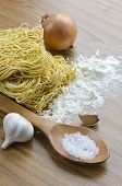 picture of egg noodles  - Three eggs and dry egg noodles on the kitchen table and a napkin with a wooden spoon - JPG