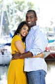stock photo of black american  - Young romantic couple hugging and standing at harbor - JPG