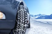 pic of icy road  - Car with mounted snow chains in wintry environment - JPG