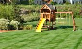 pic of swingset  - Back Yard Wooden Swing Set on Green Lawn - JPG
